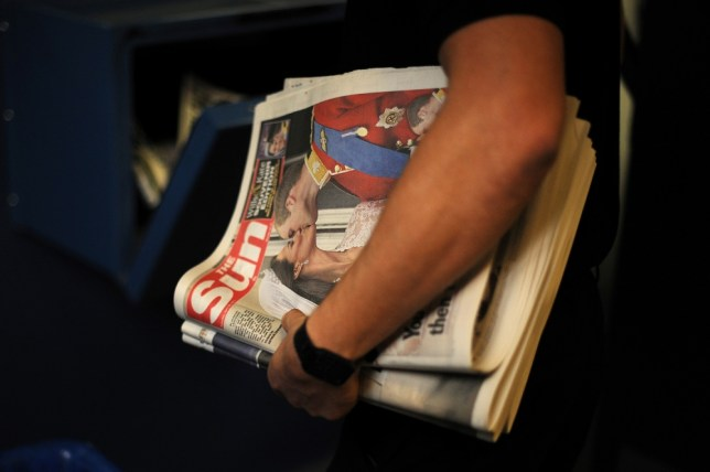 A printer carries first edition Sun newspaper copies displaying an image of Britain's Prince William and his new wife Kate on their wedding day at a newspaper printing press north of London on April 29, 2011. Prince William and Kate Middleton married today with a mix of glittering pageantry and spontaneity, kissing twice in front of a sea of revellers and breathing new life into Britain's monarchy. AFP PHOTO/BEN STANSALL (Photo credit should read BEN STANSALL/AFP/Getty Images)