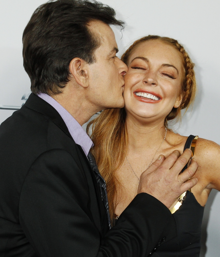 """Cast member Charlie Sheen kisses co-star Lindsay Lohan on the cheek as they pose at the premiere of their new movie """"Scary Movie 5"""" in Hollywood April 11, 2013.  REUTERS/Fred Prouser (UNITED STATES - Tags: ENTERTAINMENT)"""
