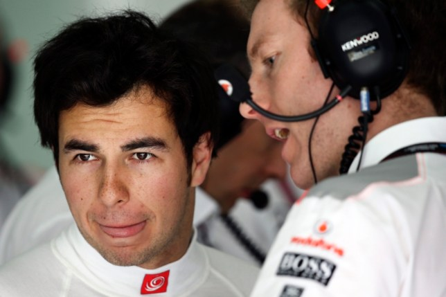 epa03668137 Mexican Formula One driver Sergio Perez of McLaren Mercedes talks to a mechanic during the first practice session at the Sakhir circuit near Manama, Bahrain, 19 April 2013. The 2013 Bahrain Formula One Grand Prix will take place on 21 April 2013.  EPA/VALDRIN XHEMAJ