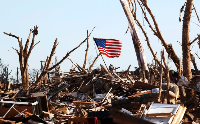 Devastated: An American flag flutters in the wind amid the rubble after the tornado ripped through Moore, Oklahoma (Picture: Reuters)