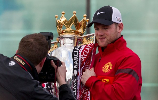 Manchester United's Wayne Rooney holds the trophy outside Old Trafford Stadium as the team prepare to parade across Manchester after winning the English Premier League, Manchester, England, Monday May 13, 2013. Manager Alex Ferguson will retire at the end of the season after more than 26 years in charge at the club. (AP Photo/Jon Super)