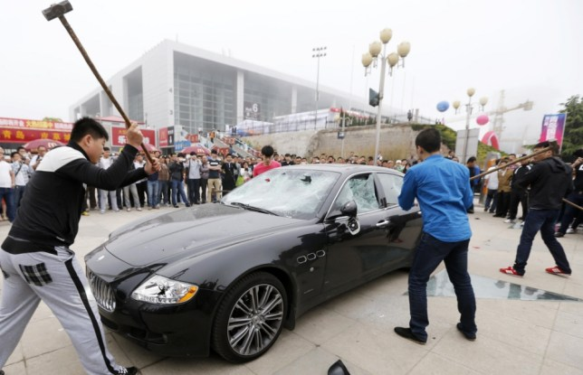 Angry Maserati owner hires men to sledgehammer his car .This picture taken on May 14, 2013 shows men using sledgehammers on a Maserati car outside the Qingdao International Convention Center which is now holding the 12th Qingdao International Auto Show, in Qingdao, east China's Shandong province. A wealthy Chinese Maserati owner hired four sledgehammer-wielding men to smash up his $420,000 supercar in protest at poor customer service, reports said on May 15.  CHINA OUT     AFP PHOTOSTR/AFP/Getty Images
