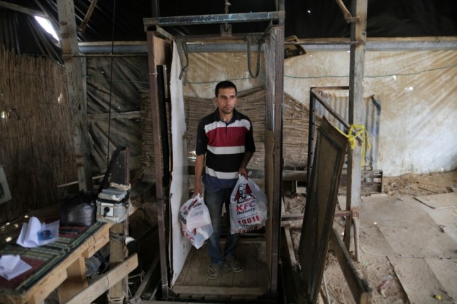 15 May 2013, Rafah, Gaza Strip --- (130515) -- GAZA, May 15, 2013 (Xinhua) -- A man comes up from the underground tunnel beneath the Gaza-Egypt border with KFC food in the southern Gaza Strip city of Rafah on May 15, 2013. Ordering fast food from one of the world's most popular restaurants KFC has become possible in Gaza after Al-Yamama delivery company started to bring the food from the Egyptian north Sinai, which borders Gaza. (Xinhua/Wissam Nassar) (djj) --- Image by © Wissam Nassar/Xinhua Press/Corbis