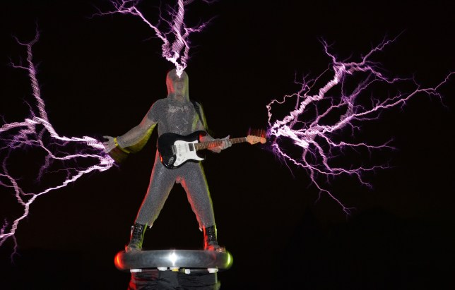 Heavy metal: Wang wears suit to perform standing on Tesla coil (Picture: AFP)