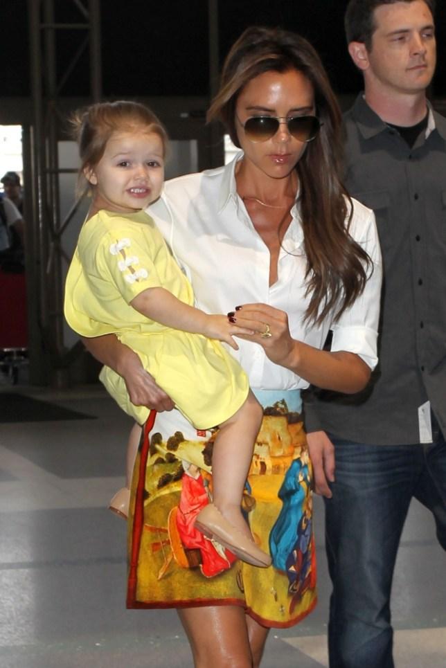 Dressed up: Victoria Beckham has put Harper in a yellow dress for a flight (Photo: XPOSUREPHOTOS.COM)