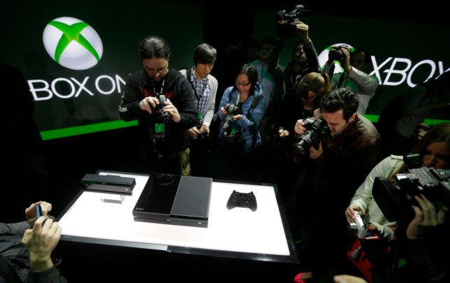 Photographers crowd around Microsoft's Xbox One console, soon to do battle with the PS4 (Picture: AP)