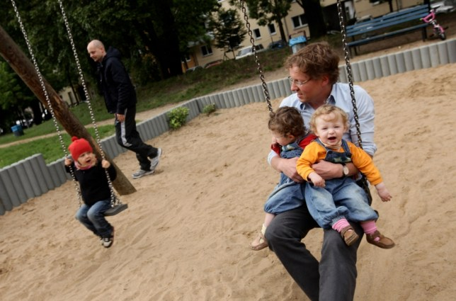 BERLIN - AUGUST 31:  Oliver H., 42, a married federal employee on 6-month paternity leave, swings with his twin 14-month-old daughters Lotte (L) and Alma at a playground on August 31, 2010 in Berlin, Germany. Under German law married couples may take 14 months parent leave, to be divided between the two spouses, during which an individual receives two thirds of his or her normal income from the state, up to EUR 1,800 a month. In order to encourage more fathers to take paternity leave, German Family Minister Kristina Schroeder is seeking to lengthen parent leave from the current 14 months to 16 months, though German Finance Minister Wolfgang Schaeuble sees the measure as too expensive.  (Photo by Sean Gallup/Getty Images)