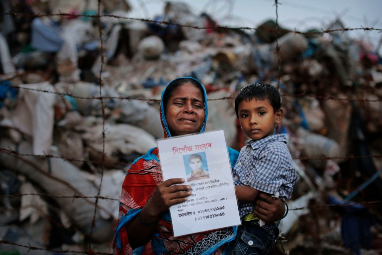 a woman cries and she holds her child in one hand and a picture of her husband in the other