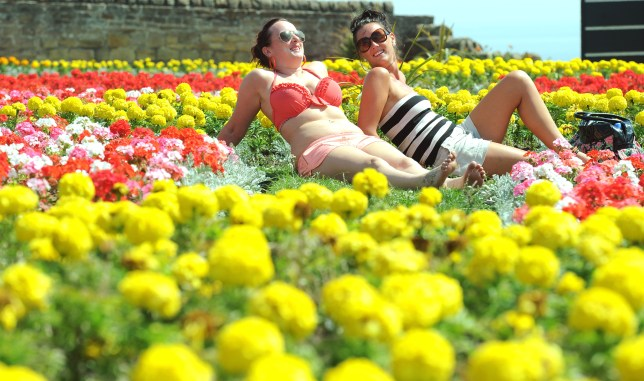 Two sisters enjoy the warm temperatures in Gateshead. The hot weather could continue for another fortnight (Picture: PA/Owen Humphreys)