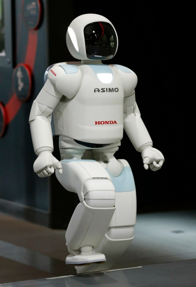 Honda Motor Co.ís interactive robot Asimo walks up a set of stairs during at a demonstration event at the Miraikan science museum, in Tokyo, Wednesday, July 3, 2013. The walking, talking interactive robot ran into glitches in its new job as a museum guide in Tokyo.  During Wednesday's demonstration, the bubble-headed Asimo machine had problems telling the difference between people raising their hands to ask questions and those aiming their smartphones to take photos at the Miraikan science museum.  (AP Photo/Shizuo Kambayashi)