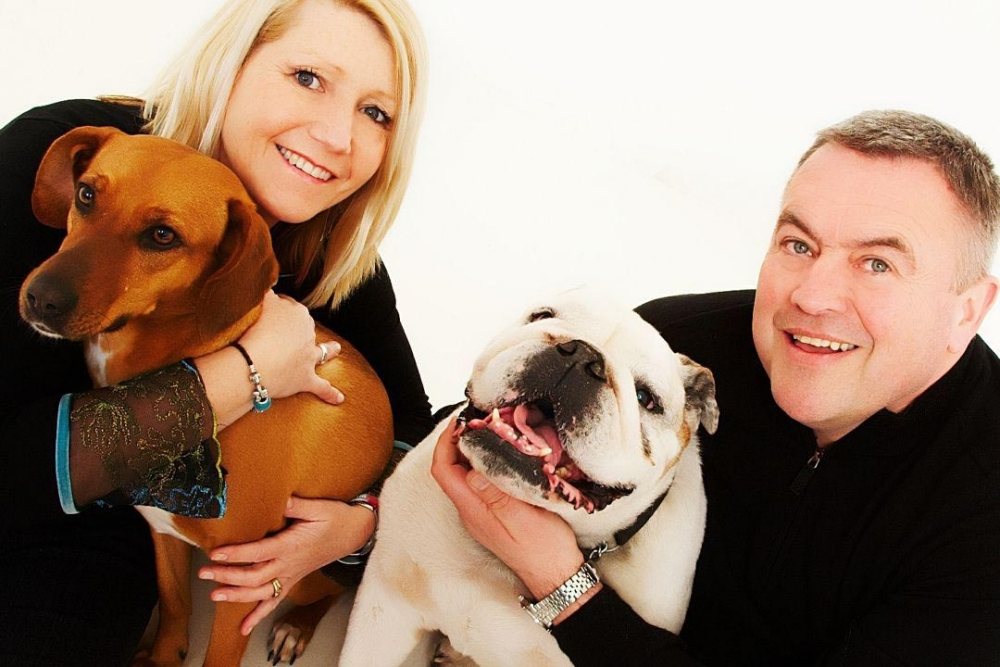 BPM MEDIA; Pictured are Tony and Sandi Lewis, parents of Pte Conrad Lewis who was killed in Afghanistan in 2011, with bulldog Fergie and mongrel Pegasus. COPY; THE faithful companion of a Warwick soldier killed in Afghanistan pines over her masterís battledress in a poignant photo commissioned by his family. Paratrooper Conrad Lewis, 22, adopted the stray mongrel in Helmand Province in 2010 and called her Pegasus ñ in honour of the Parachute Regimentís winged horse emblem. He fed Peg his rations and the pair were inseparable, so much so that Conrad had always told his family he wanted to bring her home after his tour of duty. So after he was shot and killed by a Taliban sniper while on foot patrol in February 2011, Conradís family were determined to honour his wishes and hatched a daring plan to smuggle Peg out of the country. For more info see BPMSOLDIER or call 01212345168