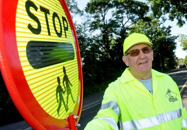 BPM MEDIA; Pictured is Lollipop man Roger Green, 64, who has been banned for high fiving pupils. COPY; A POPULAR lollipop man has been banned from high-fiving schoolchildren because ìit puts them at risk and confuses driversî, according to healthy and safety bosses. Shocked parents of upset children have hit out at Bracknell Forest Council after Roger Green was told he could no longer offer the friendly gesture to youngsters outside Sandy Lane Primary School, Bracknell, Berkshire. Roger, from Great Hollands, Bracknell,said he was told at his annual assessment with his council boss last month he could no longer high-five children because a driver complained it was slowing down traffic. The 64-year-old said: ìI put a sign up for couple of days saying that due to a complaint I could no longer high-five children. For more info see BPMHIGHFIVE or call 01212345168