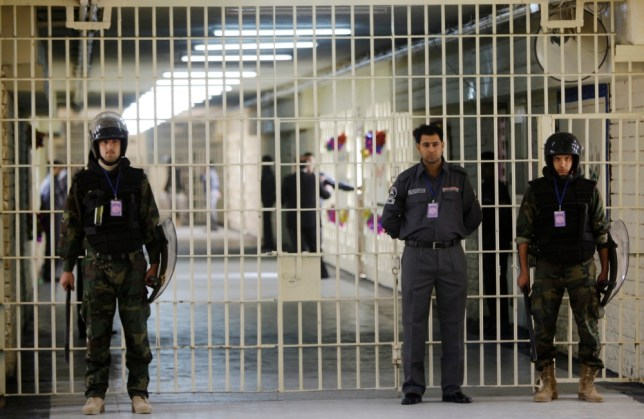 FILE - In this Feb. 21, 2009 file photo, guards stand at a cell block at the renovated Abu Ghraib prison, now renamed Baghdad Central Prison and run by Iraqis in Baghdad, Iraq. Late-night jailbreak attempts at two major prisons outside Baghdad have killed dozens, including at least 25 members of Iraqís security forces who battled militants armed with car bombs, mortars and machine guns, officials said Monday. (AP Photo/Karim Kadim, File)