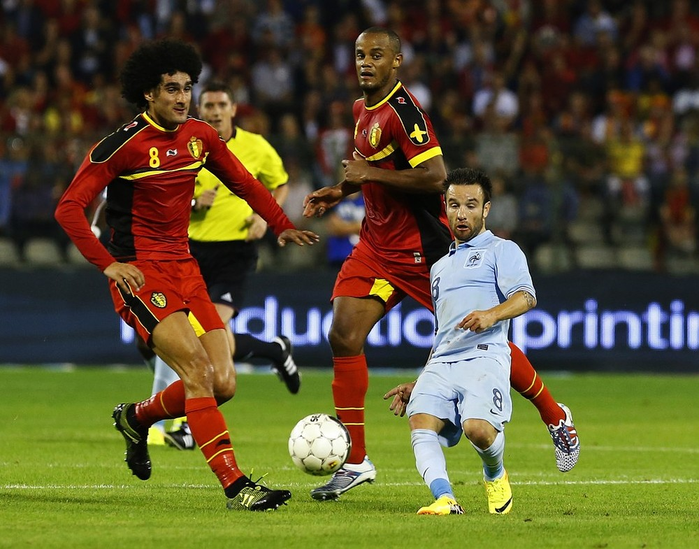 France's Mathieu Valbuena gets dwarfed by Belgium's Premier League giants Marouane Fellaini and Vincent Kompany