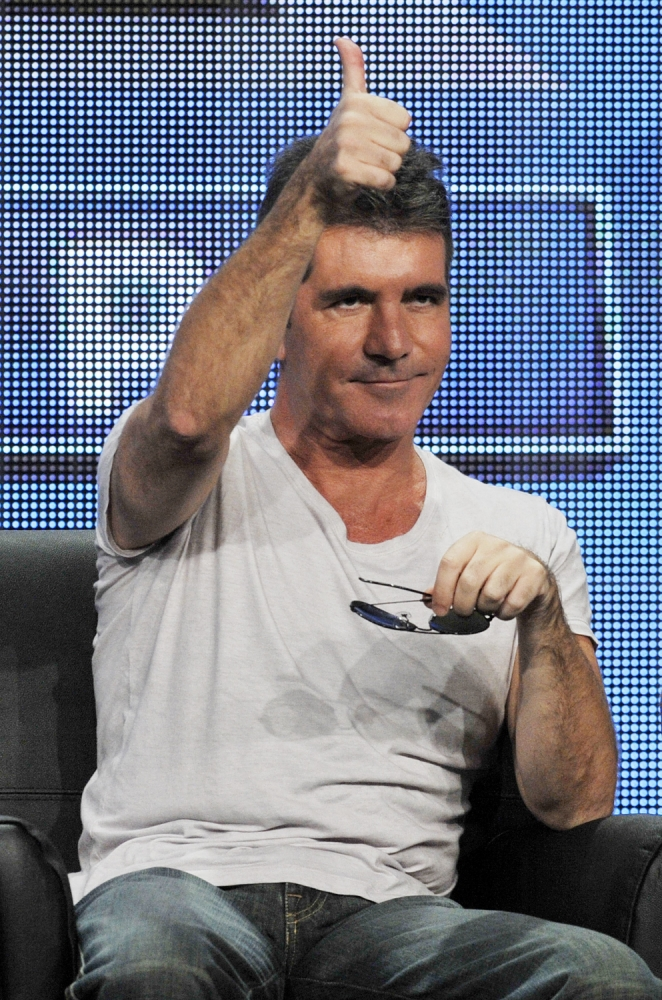 """Simon Cowell, a judge on the FOX series """"The X Factor,"""" gives a thumbs-up to reporters following a panel discussion on the show at the FOX 2013 Summer TCA press tour at the Beverly Hilton Hotel on Thursday, Aug. 1, 2013, in Beverly Hills, Calif. (Photo by Chris Pizzello/Invision/AP)"""