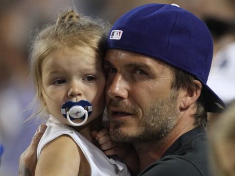 David Beckham struggles to keep his daughter Harper under control at Los Angeles baseball game