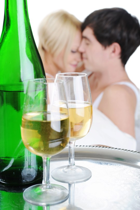 Young couple drinking champagne in bed.