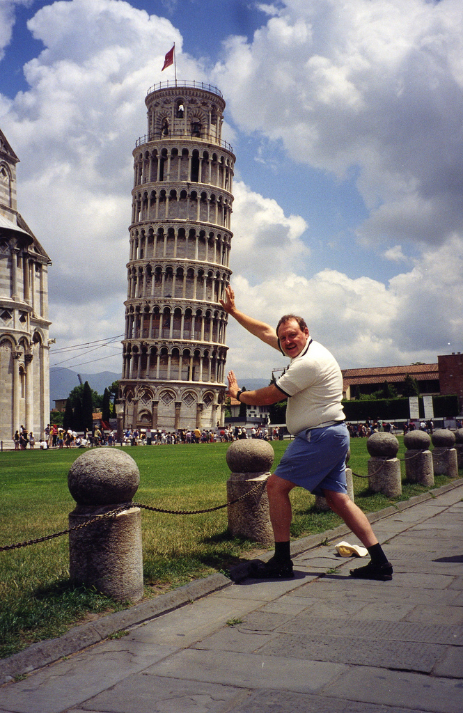 Man leans on Tower of Pisa