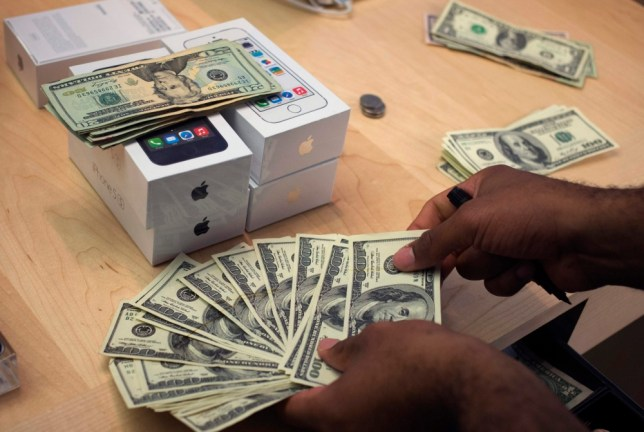 A cashier counts U.S. dollars next to five new Apple iPhone 5S phones at the Apple Retail Store on Fifth Avenue in Manhattan, New York September 20, 2013. Apple Inc's newest smartphone models hit stores on Friday in many countries across the world. REUTERS/Adrees Latif   (UNITED STATES - Tags: BUSINESS TELECOMS)