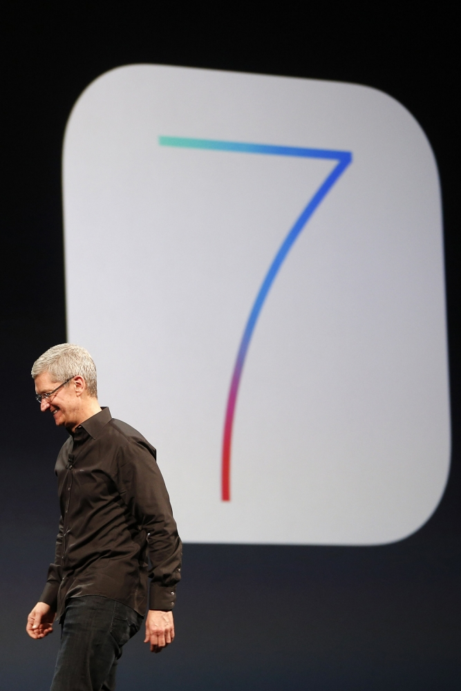 Apple Inc. CEO Tim Cook walks past an iOS7 logo during the Apple Worldwide Developers Conference (WWDC) 2013 in San Francisco, California June 10, 2013. REUTERS/Stephen Lam (UNITED STATES - Tags: BUSINESS SCIENCE TECHNOLOGY)