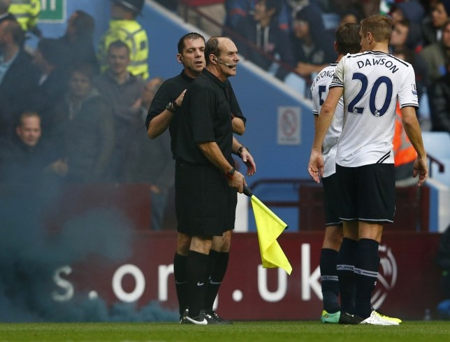 Referee Phil Dowd (L) checks the back of the assistant referee (C) after a smoke canister was thrown onto the pitch during their English Premier League soccer match against Aston Villa at Villa Park in Birmingham, northern England October 20, 2013. REUTERS
