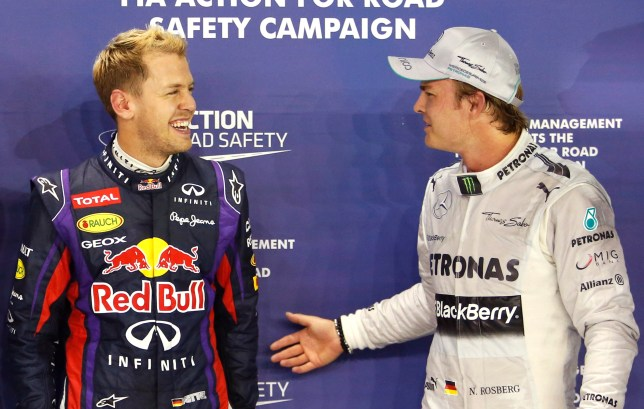 Red Bull Formula One driver Vettel and Mercedes Formula One driver Rosberg stand together after the qualifying session of the Singapore F1 Grand Prix in Singapore