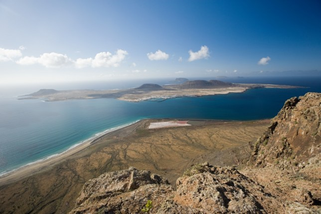 The rocky terrain of Lanzarote, with La Graciosa just off the northern tip of the island (Picture: Alamy)