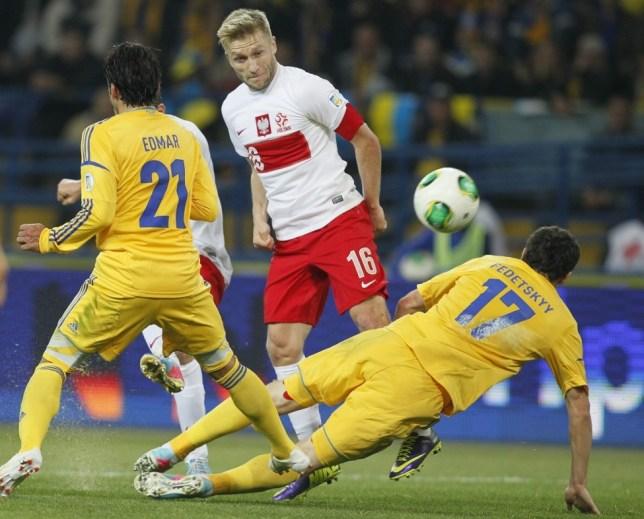 epa03906277 Polish player Jakub Blaszczykowski (C) fights for the ball with Artem Fedetskiy (R) of Ukraine during their World Cup 2014 qualification match Ukraine vs Poland in Kharkiv, Ukraine, 11 October 2013.  EPA/SERGEY DOLZHENKO