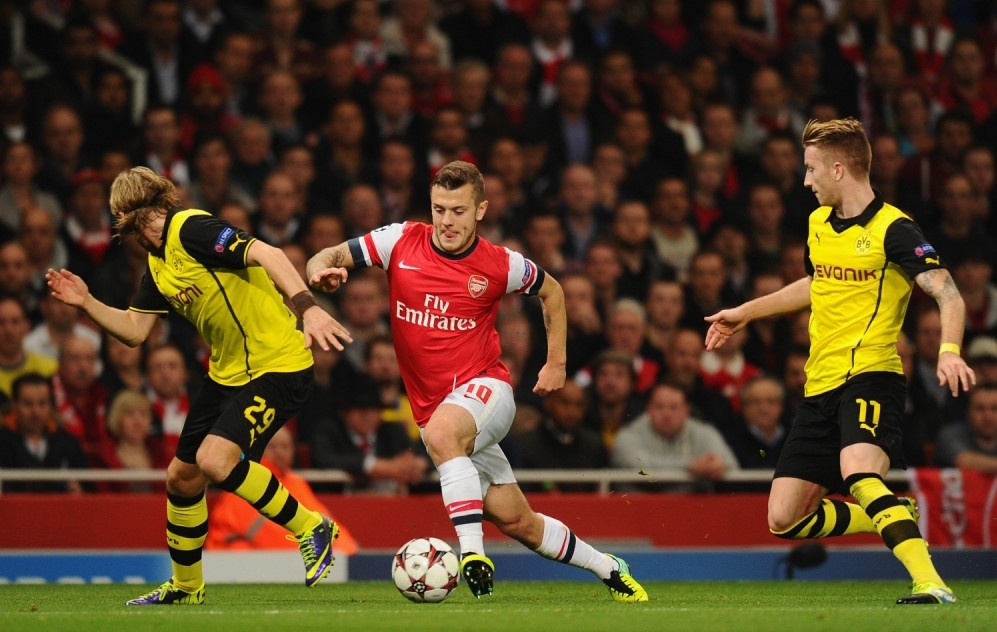LONDON, ENGLAND - OCTOBER 22: Jack Wilshere of Arsenal goes through Marco Reus of Borussia Dortmund and Marcel Schmelzer of Borussia Dortmund  during the UEFA Champions League Group F match between Arsenal and  Borussia Dortmund at Emirates Stadium on October 22, 2013 in London, England.  (Photo by Mike Hewitt/Bongarts/Getty Images)
