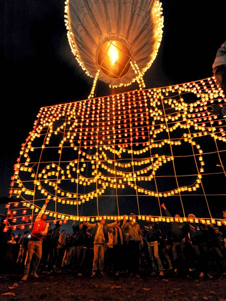In this Saturday, Nov. 16, 2013, Shan locals ease a hot-air balloon decorated with hundreds of candles into position as it takes off in front of the Sulamuni Buddhist Pagoda in Shan State, Myanmar. The Tazaungdaing Lighting Festival is held each year in celebration of the end of the rainy season. (AP Photo/Philip Heijmans)