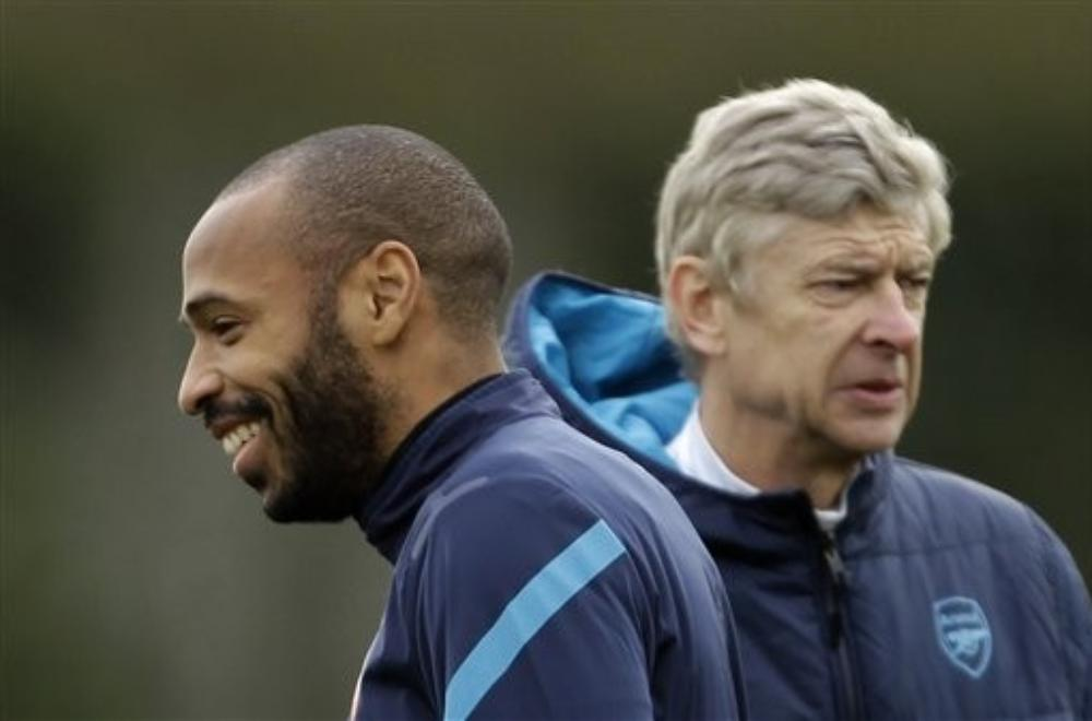 Arsenal's on loan former player, and the club's all time highest scorer, Thierry Henry, left, stands near the club's French manager Arsene Wenger during a training session at the club's facilities in London Colney, England, Tuesday, Feb. 14, 2012. Arsenal are due to play AC Milan in the first leg of their Champions League last 16 soccer match in Milan on Wednesday. Matt Dunham/AP