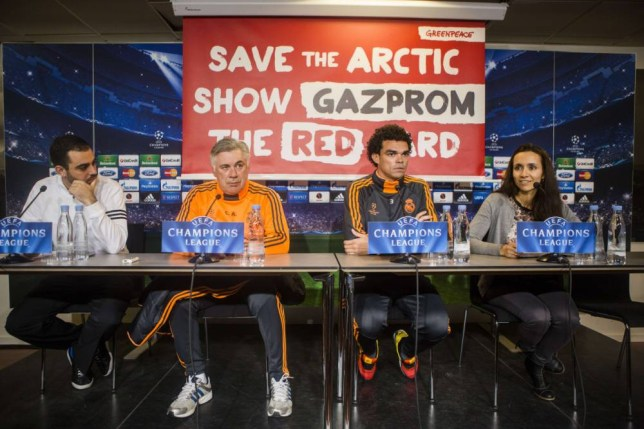 A Greenpeace banner is seen during a press conference given by Real Madrid head coach Carlo Ancelotti (2ndL) and Real Madrid defender Pepe (2ndR) at Parken stadium in Copenhagen, Denmark, on December 9, 2013. Real Madrid will face FC Copenhagen in a UEFA Champions League group B football match on December 10, 2013. Seen left is an official from Real Madrid and seen right is an interpreter.   AFP PHOTO / Scanpix Denmark /NIKOLAI LINARES / Denmark outNikolai Linares/AFP/Getty Images
