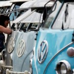 A visitor looks at Volkswagen Kombi minibus models during a Kombi fan club meeting in Sao Bernardo do Campo December 8, 2013. Volkswagen Brazil, the last plant to produce the Kombi, will cease production of the iconic vehicle on December 20 after 56 years of production. Higher manufacturing costs and increase in production time due to new auto regulations, which will require anti-lock brake systems and air bags in all cars produced in Brazil from 2014, contributed to its decision to stop the production of the Kombi, according to the company.   Picture taken December 8, 2013. REUTERS/Paulo Whitaker (BRAZIL - Tags: TRANSPORT SOCIETY BUSINESS)