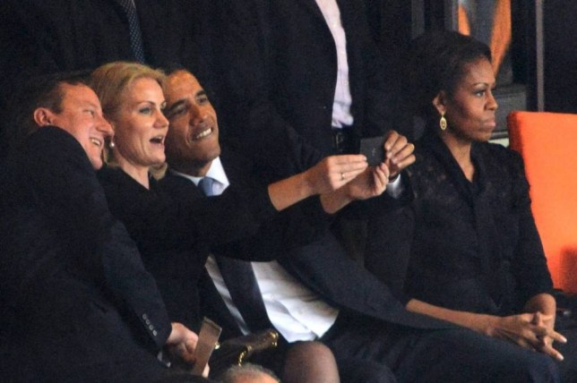 ALTERNATIVE CROP US President  Barack Obama (R) and British Prime Minister David Cameron pose for a picture with Denmark's Prime Minister Helle Thorning Schmidt (C) next to US First Lady Michelle Obama (R) during the memorial service of South African former president Nelson Mandela at the FNB Stadium (Soccer City) in Johannesburg on December 10, 2013. Mandela, the revered icon of the anti-apartheid struggle in South Africa and one of the towering political figures of the 20th century, died in Johannesburg on December 5 at age 95.   AFP PHOTO / ROBERTO SCHMIDTROBERTO SCHMIDT/AFP/Getty Images