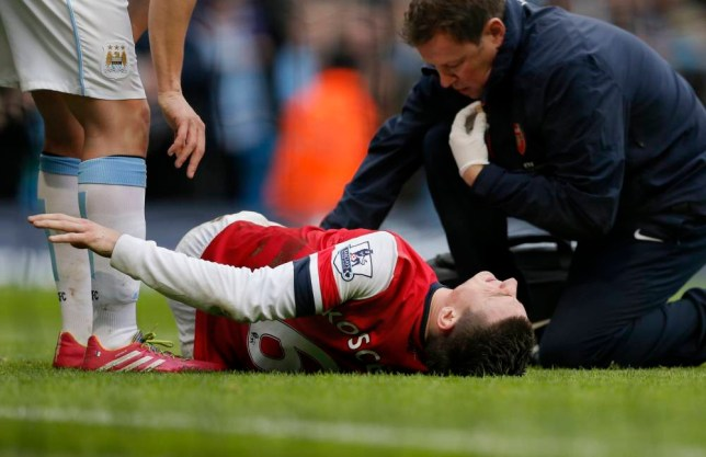 "Arsenal's Laurent Koscielny reacts as he treated for an injury during their English Premier League soccer match against Manchester City at the Etihad stadium in Manchester, northern England December 14, 2013. REUTERS/Phil Noble (BRITAIN - Tags: SPORT SOCCER) NO USE WITH UNAUTHORIZED AUDIO, VIDEO, DATA, FIXTURE LISTS, CLUB/LEAGUE LOGOS OR ""LIVE"" SERVICES. ONLINE IN-MATCH USE LIMITED TO 45 IMAGES, NO VIDEO EMULATION. NO USE IN BETTING, GAMES OR SINGLE CLUB/LEAGUE/PLAYER PUBLICATIONS. FOR EDITORIAL USE ONLY. NOT FOR SALE FOR MARKETING OR ADVERTISING CAMPAIGNS"