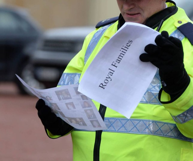 A policeman checks A crib sheet for the Royal Family as they arrive at the Queen's Christmas lunch at Buckingham Palace for her extended family