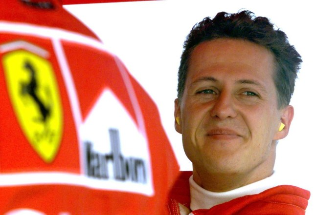 Germany's Michael Schumacher smiles in the pit area after completing his second qualifying session of the Hungarian Formula One Grand Prix in this August 15, 1998 file photo. Ferrari fans held a vigil for Michael Schumacher on his 45th birthday on January 3, 2014, gathering outside the French hospital where the seven times world champion continued to fight for his life after a skiing accident. Schumacher's family thanked the fans in a statement on Friday evening saying they were moved to tears while French media reported that investigators were studying a camera the German had on him at the time of the accident. REUTERS/Radu Sigheti/Files (HUNGARY - Tags: SPORT MOTORSPORT F1) Radu Sigheti/Reuters