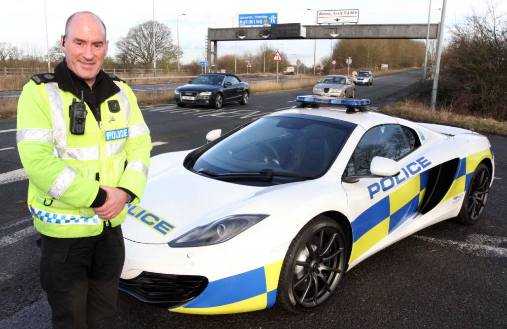 PC Angus Nairn poses with the McLaren Spider 12C - Britain's fastest police car