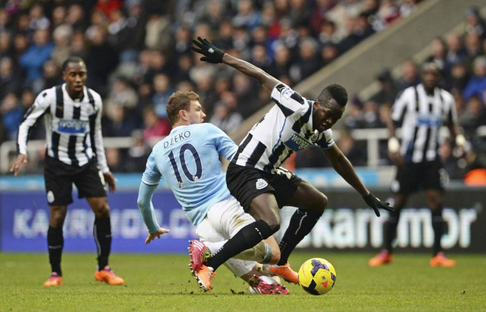 """Newcastle United's Cheick Tiote (R) is challenged by Manchester City's Edin Dzeko during their English Premier League soccer match at St James' Park in Newcastle, northern England, January 12, 2014. REUTERS/Nigel Roddis (BRITAIN - Tags: SPORT SOCCER) NO USE WITH UNAUTHORIZED AUDIO, VIDEO, DATA, FIXTURE LISTS, CLUB/LEAGUE LOGOS OR """"LIVE"""" SERVICES. ONLINE IN-MATCH USE LIMITED TO 45 IMAGES, NO VIDEO EMULATION. NO USE IN BETTING, GAMES OR SINGLE CLUB/LEAGUE/PLAYER PUBLICATIONS. FOR EDITORIAL USE ONLY. NOT FOR SALE FOR MARKETING OR ADVERTISING CAMPAIGNS"""