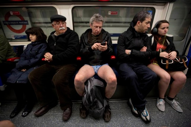 """People take part in the """"No Trousers Tube Ride"""" event next to other passengers on an underground train passing through King's Cross station in London, Sunday, Jan. 12, 2014.  The stunt was held to coincide with the """"Global No Pants Subway Ride"""", where passengers board subway cars in the middle of winter without wearing trousers and act normally.  (AP Photo/Matt Dunham)"""