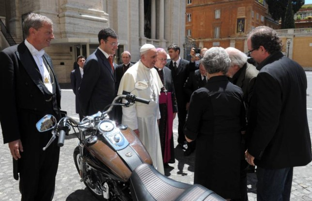 epa04018520 A handout picture provided by Osservatore Romano on 13 January 2014 shows Pope Francis (C) being presented with a Harley Davidson Dyna Super Glide motorcycle in Vatican City, the Vatican, 12 June 2013. According to Bonhams auction house, the motorcycle signed by the Pontiff will be auctioned for charity on 06 February 2014.  EPA/OSSERVATORE ROMANO / HANDOUT BEST QUALITY AVAILABLE HANDOUT EDITORIAL USE ONLY/NO SALES
