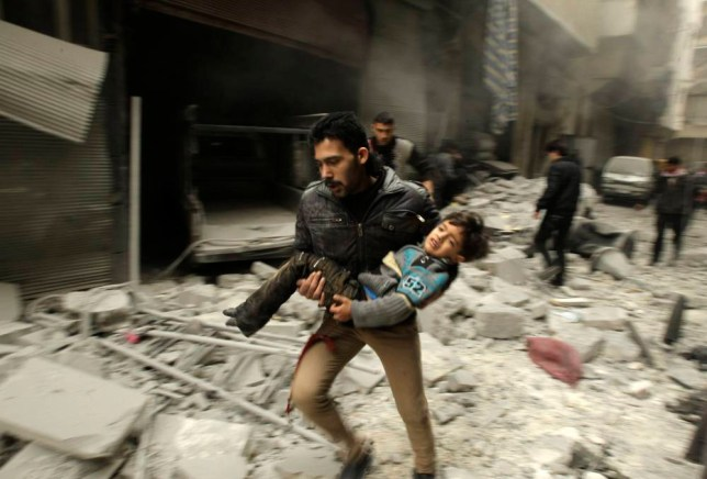 A man runs as he carries a child who survived from what activists say was an airstrike by forces loyal to Syrian President Bashar al-Assad, at al-Ferdaws in Aleppo January 21, 2014. REUTERS/Ammar Abdullah (SYRIA - Tags: POLITICS CIVIL UNREST CONFLICT)