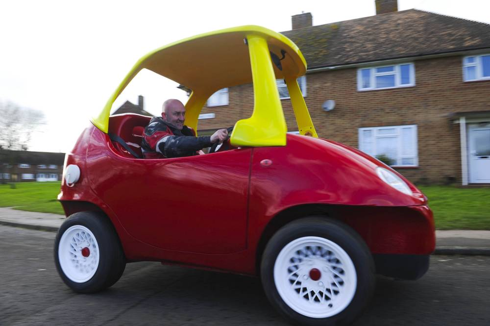 PIC BY DAN ROWLANDS / CATERS NEWS (PICTURED: JOHN DRIVING THE TOY TOWN COUPE)- A mechanic has created an adult version of classic kids car the cozy coupe - which cost a whopping £35,000. Petrolhead John Bitmead spent five months creating a life-size version of the tots toy - and copied every detail from the yellow roof, to glassless windows and over-sized drinks holder. And although the kids version is well-known for running on pedal power, Johns newest toy can do 0 -60 in just 17 seconds - and has an 800cc engine. SEE CATERS COPY