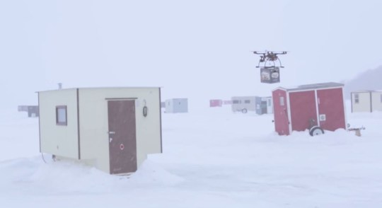 The drone swoops down with beer to a fishermen's hut on a frozen late (Picture: YouTube)
