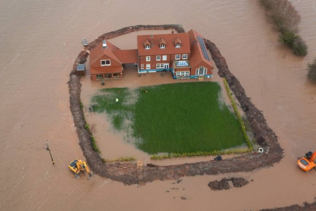 Sam Notaro is beginning to lose his battle to shield his home from floods. The waters have seeped under his 5ft earth barrier (Picture: SWNS)
