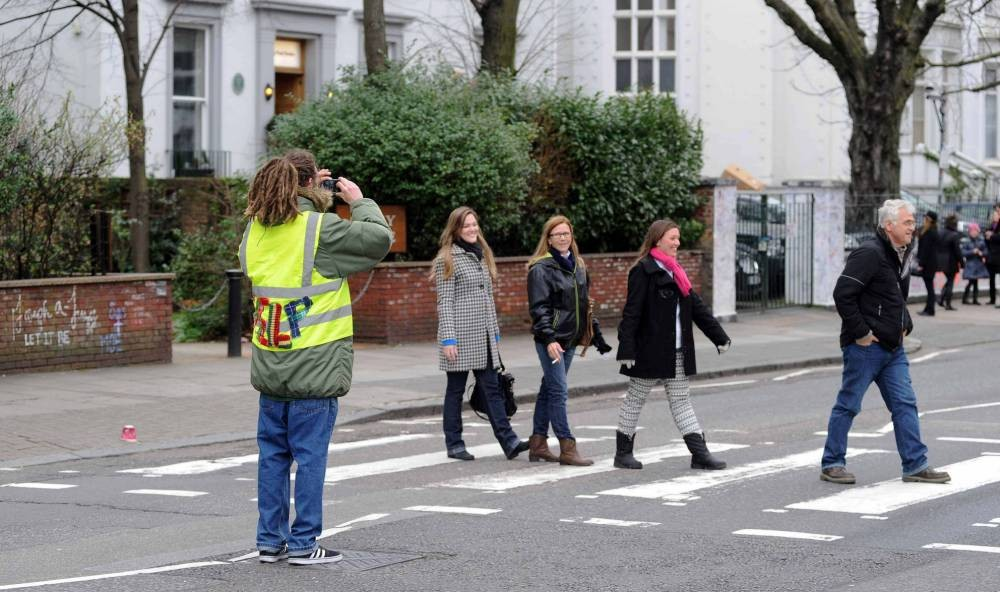 Mandatory Credit: Photo by Frank Doran/REX (3601732j)  Man wearing official looking high vis jacket charges tourists to take pictures of themselves at the Abbey Road zebra crossing  Man charges tourists to take pictures of themselves at the Abbey Road zebra crossing, Abbey Road Studios, London, Britain - 26 Feb 2014  An enterprising local appears to have come up with a cheeky money making scheme utilising the famous zebra crossing outside Abbey Road studios in London. With hordes of tourists wishing to recreate the famous moment The Beatles posed on the crossing, one unidentified man has decided to cash in. Wearing a yellow vest, with 'help' stitched on the back in fabric, the man offers to take photos for the eager visitors. Using their own cameras and phones, he charges the groups GBP 4 a pop to take the snaps for them.