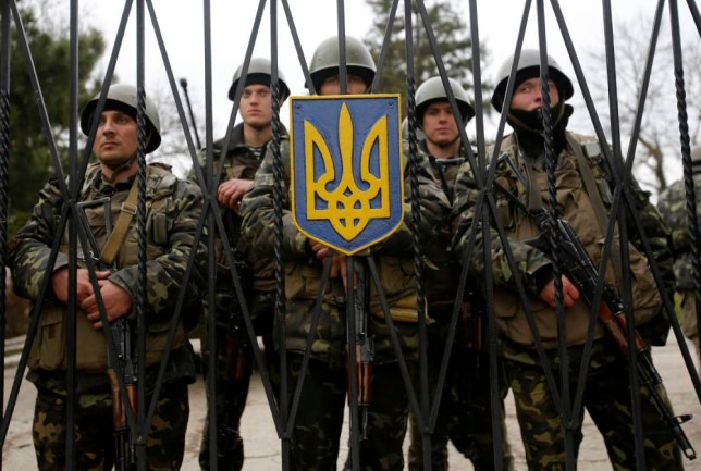 Ukrainian soldiers guard a gate of an infantry base in Privolnoye, Ukraine, Sunday, March 2, 2014. Hundreds of unidentified gunmen arrived outside Ukraine's infantry base in Privolnoye in its Crimea region. The convoy includes at least 13 troop vehicles each containing 30 soldiers and four armored vehicles with mounted machine guns. The vehicles ó which have Russian license plates ó have surrounded the base and are blocking Ukrainian soldiers from entering or leaving it. (AP Photo/Darko Vojinovic)