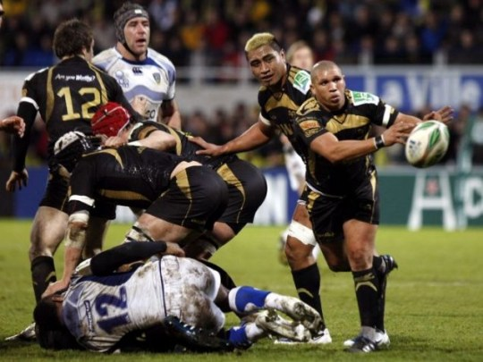 Ospreys player Ricky Januarie, right, throws the ball as teammate Jerry Collins, second right, looks on during their European Cup rugby union match in Clermont Ferrand