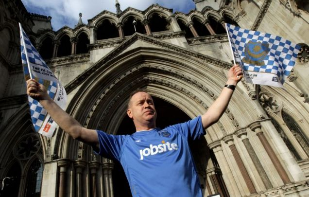 Portsmouth football club fan David Maples waves a club flags outside the High Court