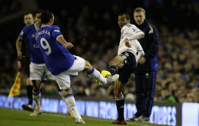 Chelsea's Ashley Cole, second right, injures himself in a tackle with Everton's Landon Donovan